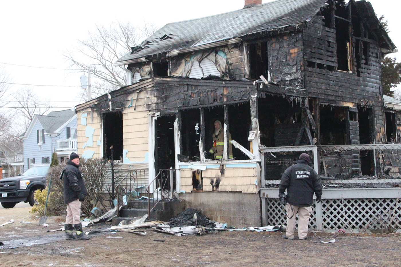 A TOTAL LOSS: The charred remnants of the house on Strand Avenue were all that remained after a fire engulfed the property early Monday morning. Here, state and city fire marshals investigate the scene.