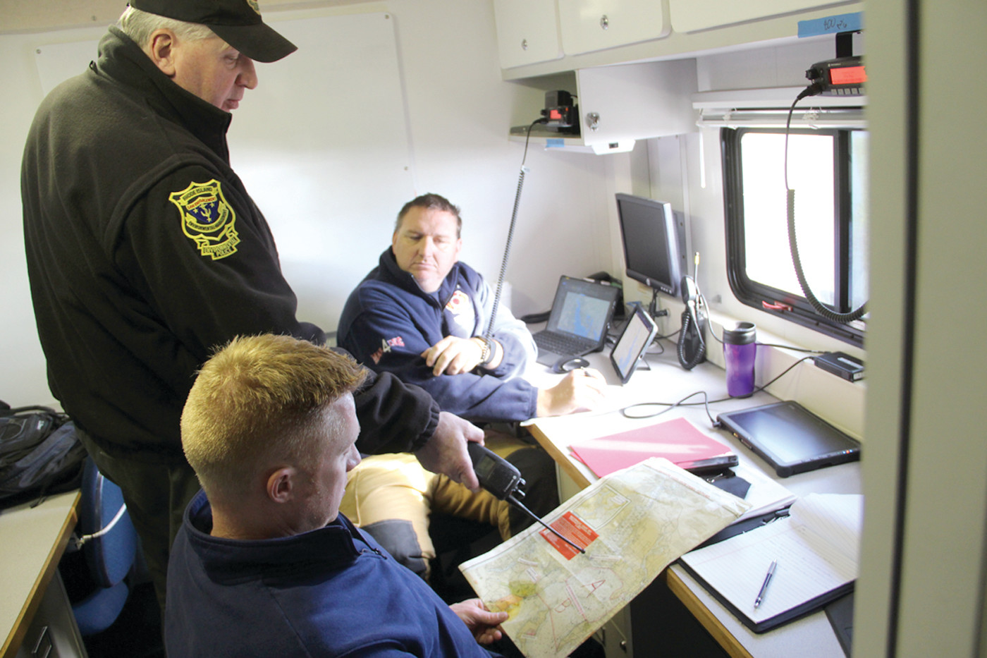 COORDINATING SEARCH: Kurt Blanchard of the DEM talks with Warwick firefighters Lt. Dan Bradley and Justin Vail, who managed a grid-by-grid search of bay waters conducted by as many as eight vessels.