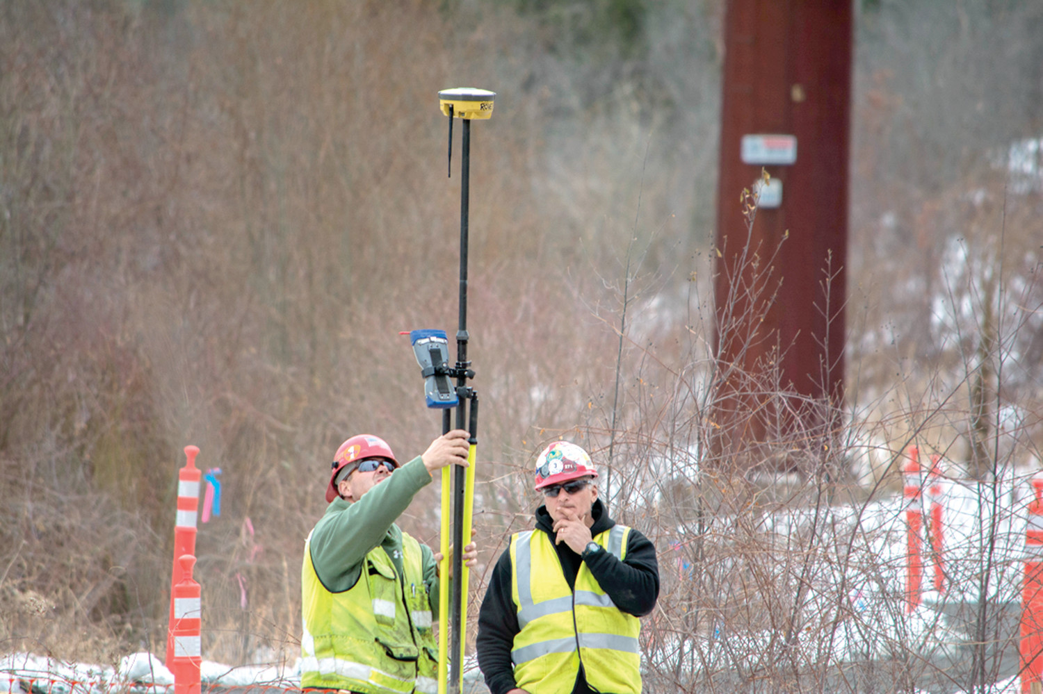 TAKING MEASUREMENTS: A crew takes readings under high-tension lines near the site for a substation.