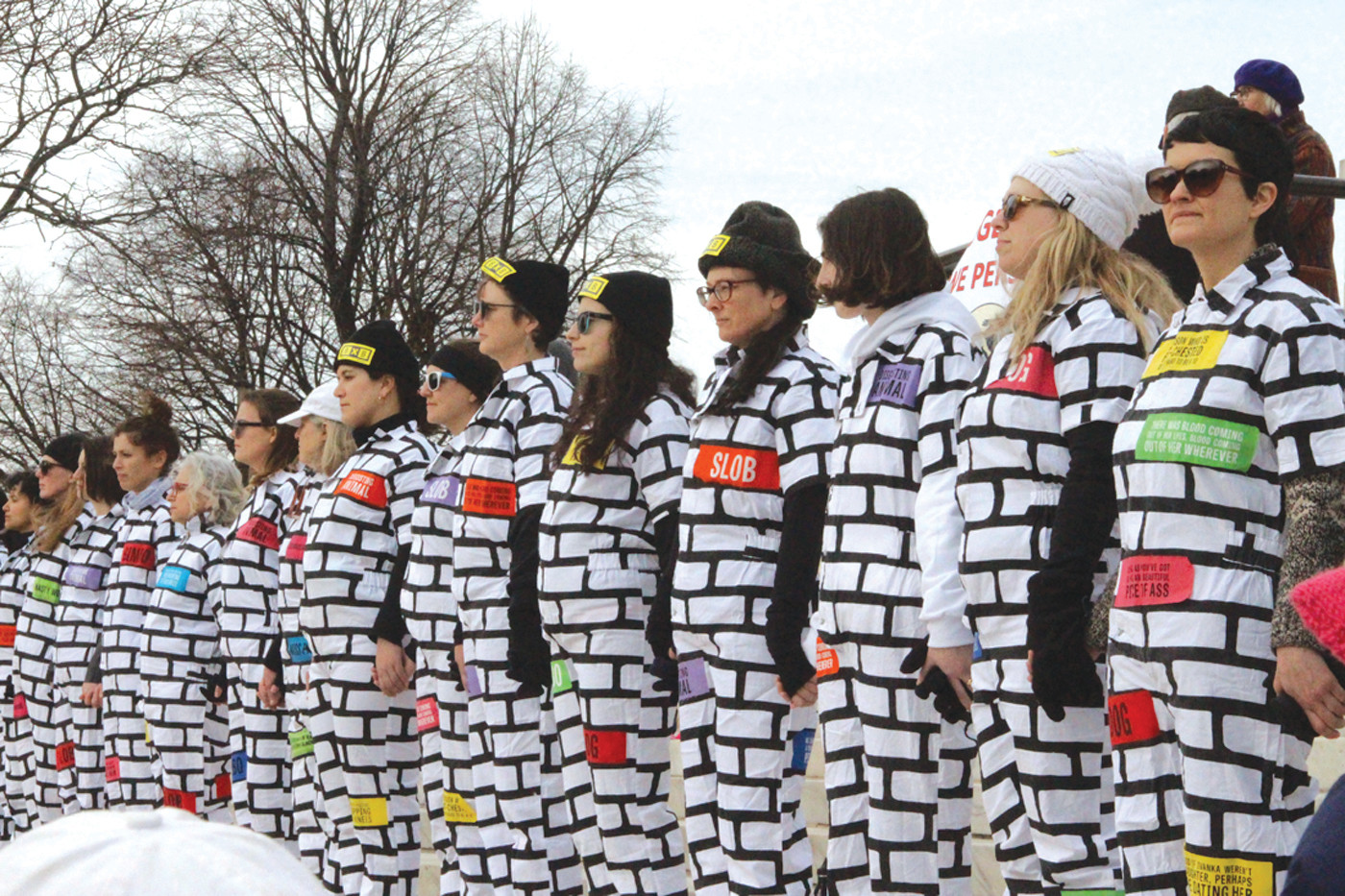 "ANOTHER BRICK IN THE WALL: Demonstrators from the national organization ""BRICK X BRICK"" showed up in force, lining the stairs of the State House in white, brick-decorated outfits symbolizing that they cannot be torn down by hateful rhetoric or misogyny."