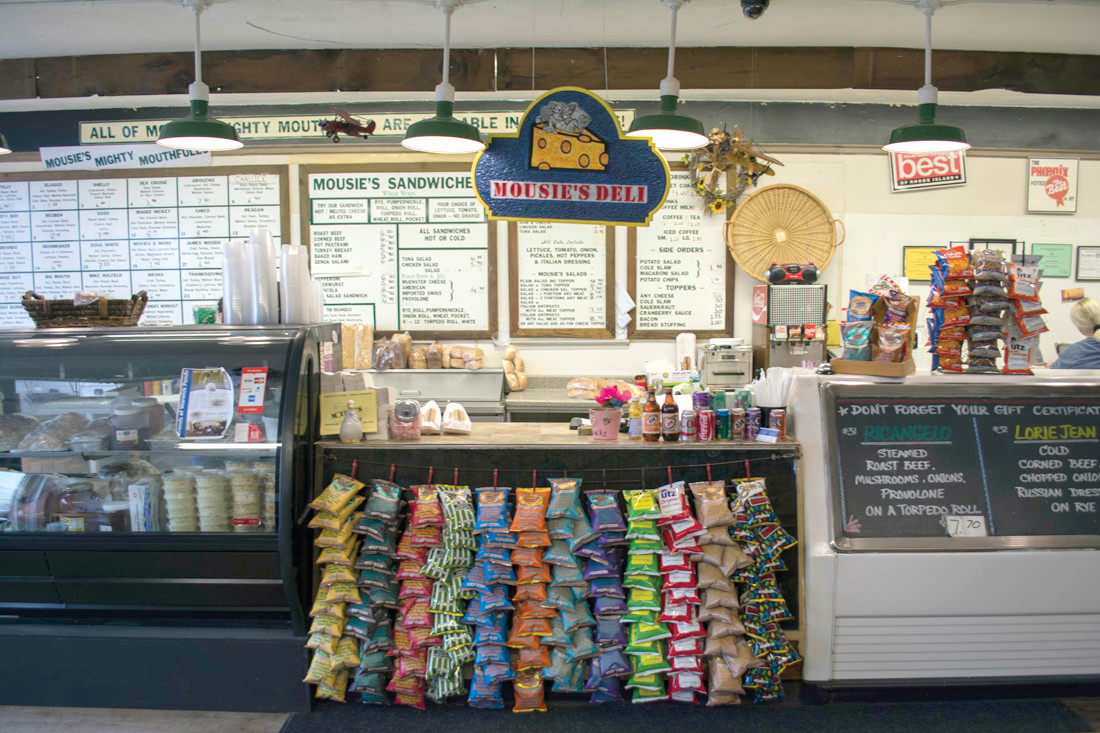 "IT'S MOUSIE'S: The deli's counter, adorned with rows of chips and produce available for wholesale in the display window. The Mousie's sign hangs above where customers order their food. The ""Mousie's Mighty Mouthfuls"" menu is displayed grid-style, alongside their other options and more conventional sandwiches."