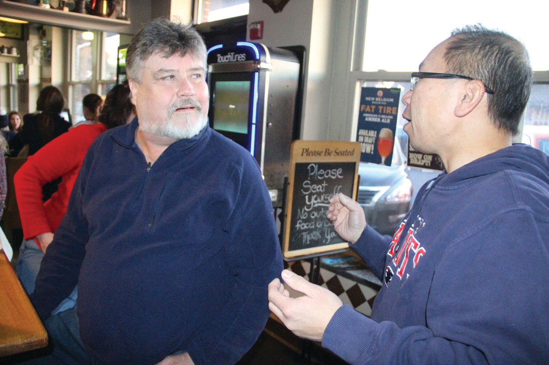 SOMETHING THEY AGREE ON: Mayor and goubernatorial candidate Allan Fung talks with Brian Finelli at Dave's Bar and Grill in a break during Sunday's Patriot game. Both are Patriot fans.