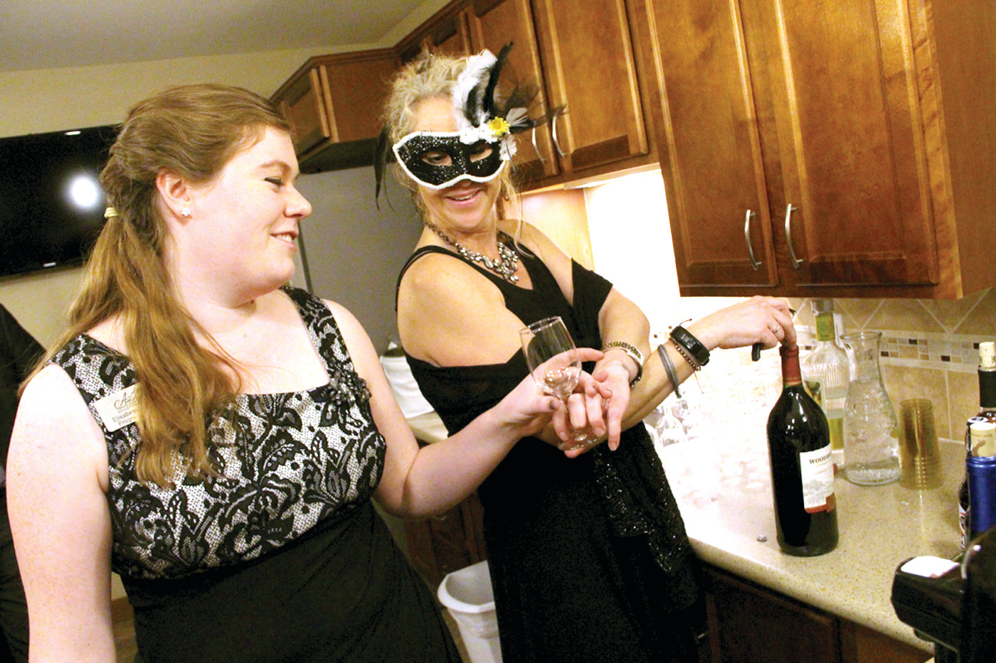 TOASTING YEAR ONE: Elisabeth Lamantia and Tina Anderson served up drinks at the first year anniversary celebration Thursday at All American Assisted Living.