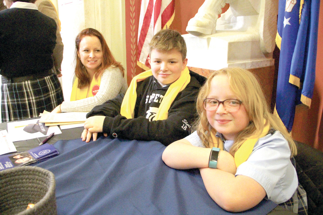 THERE TO ANSWER QUESTIONS: Robert Minnis and students Andy and Allie Short man the St. Peter School table display in the halls of the State House during Thursday's observance of National School Choice Week.
