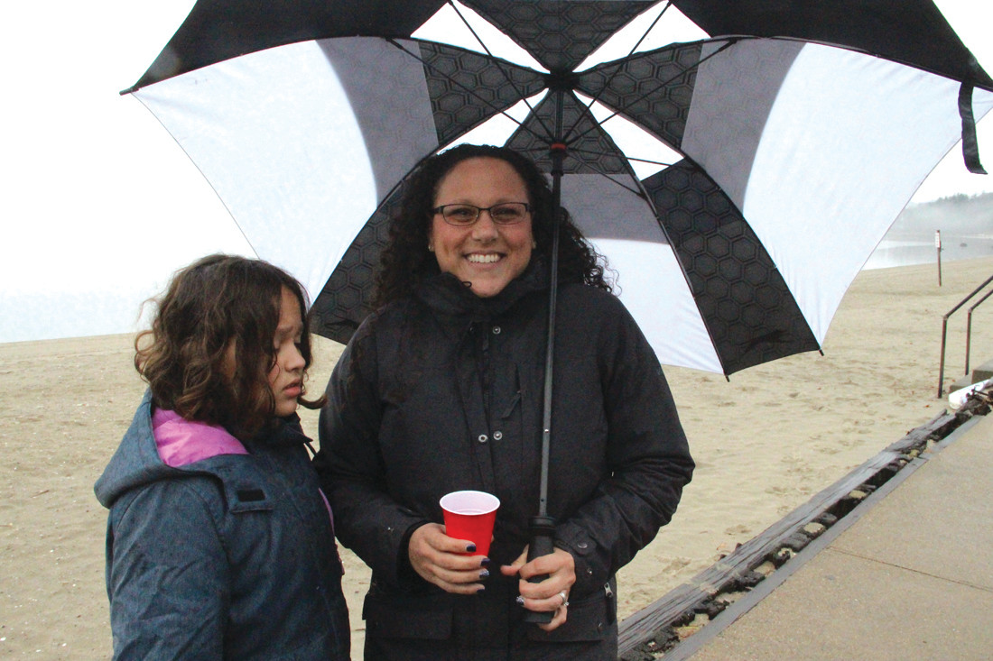 NOW THAT'S STAYING DRY: Sira and Tina Surrette sought shelter from the light rain under an umbrella while they waited to see John Surrette make the plunge. Sunday made him a three-time Frozen Clam.