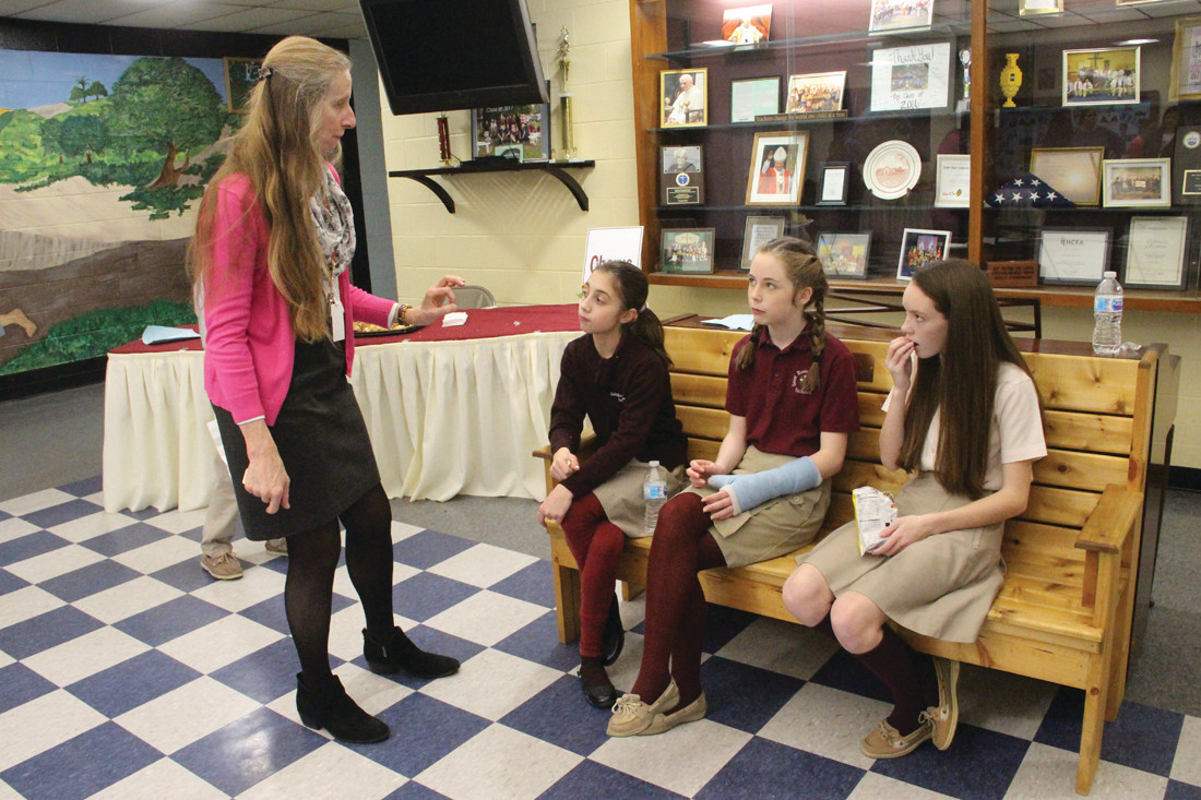 STUDENT GUIDES: Mary Morse goes over details with St. Rose of Lima School student guides Aimee Walsh, Laurel McMahon and Isabelle Powers as they wait to give tours of the school.