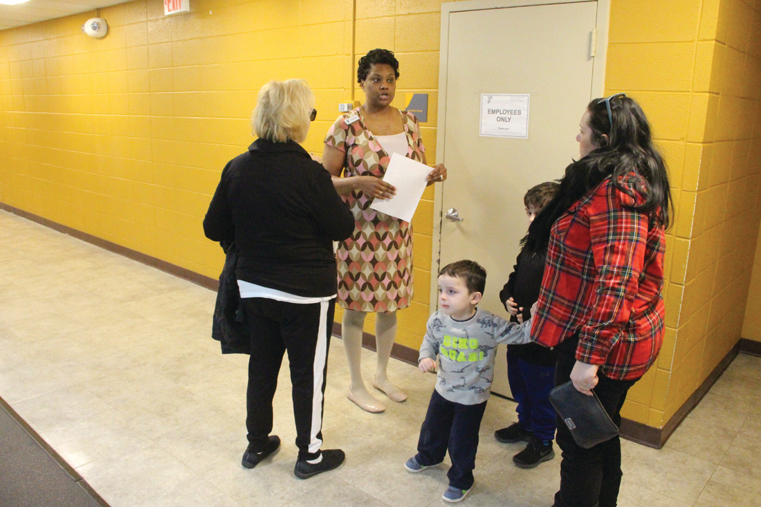 ON TOUR: Following a visit to the pool, a family follows a Y staff member as she takes them on a tour of the Kent County Y on Centerville Road.