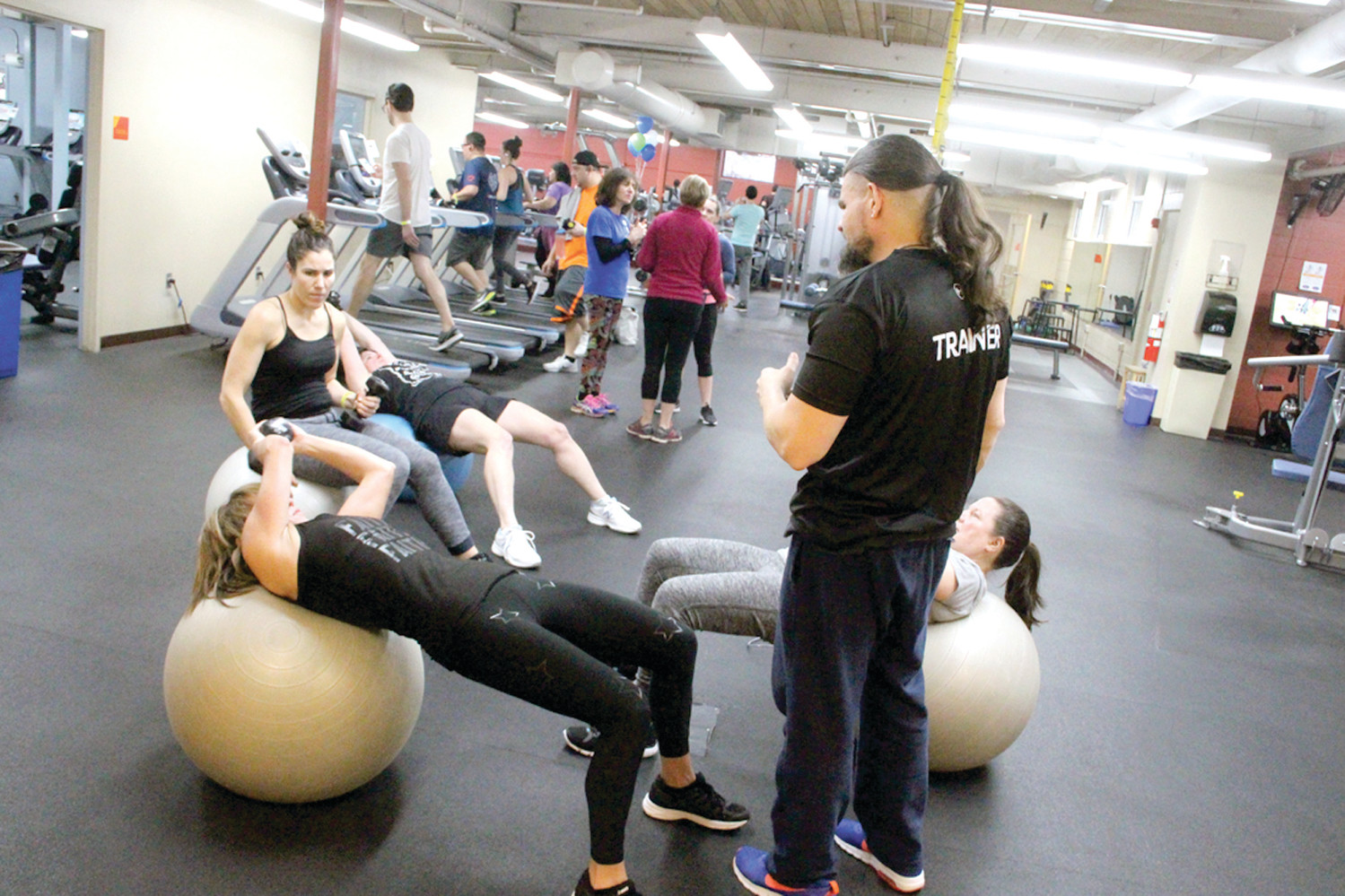 ON A ROLL: Trainer John Lorenson works with a group of four women, all Y members, going from station to station in the fitness center Saturday morning.