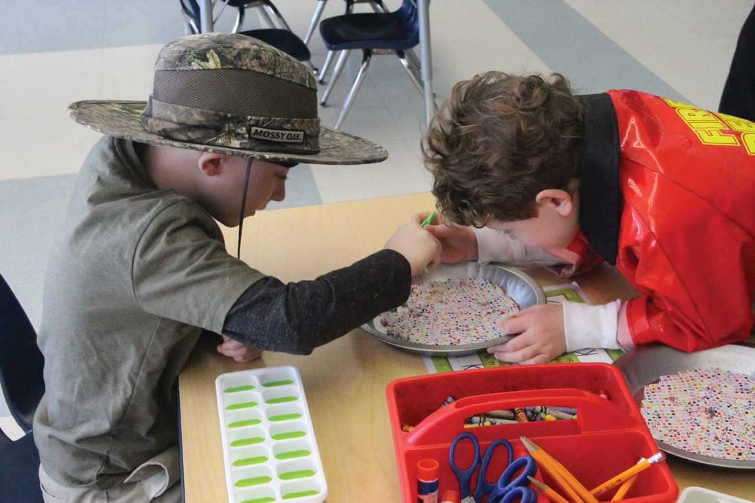"PRACTICING THEIR ABCS: Kindergarteners Corbin Kieslich, dressed as a park ranger for ""Career Day""' and Justin Krechman, dressed as a fireman, remained focused on the task at hand despite having the paparazzi around."