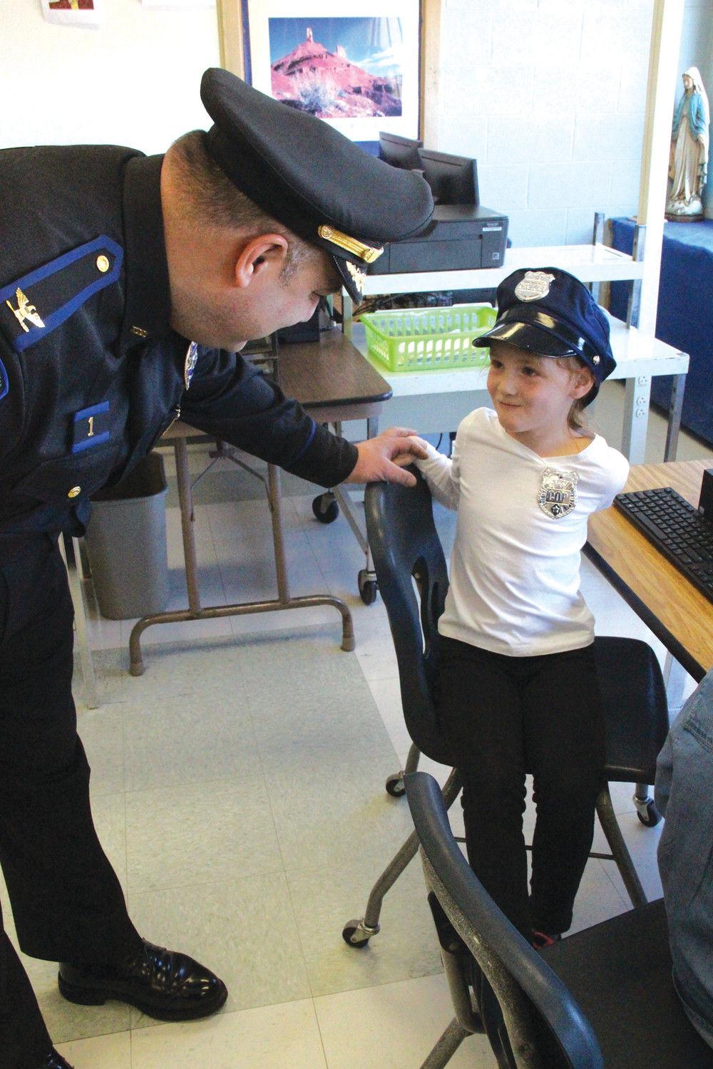 ROLE MODEL: Eliza Abedon, a kindergarten student at St. Kevin School, came dressed as a police officer for 'career day' during Catholic Schools Week. She got a chance to talk to North Providence Police Chief David Tikoian Wednesday morning.