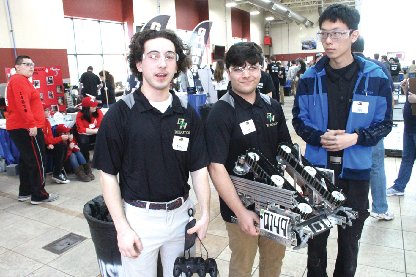 "BACK TO THE PIT: Hendricken team members Liam McKenzie, Paarth Tandon and William Chen pose for a photo before turning to ""the pit"" to tune up their robot for a second round. Team coaches are Bob Rakovic and Mark DiPiuppo."