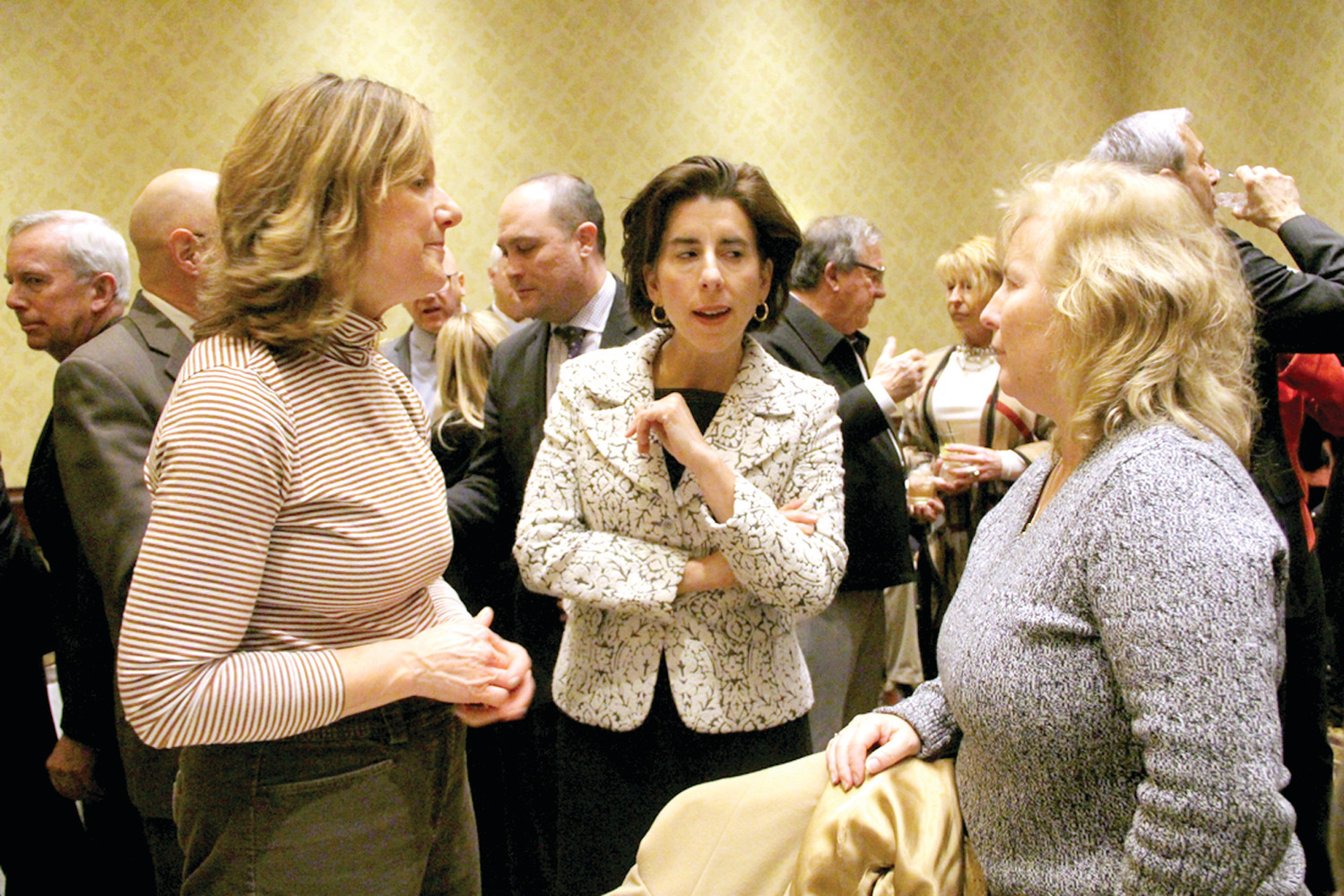 MAKING INTRODUCTIONS: Louise Marcus (left) and Melanie Flamand, both graduates of the Goldman Sachs 10,000 Small Business program, talk with Gov. Gina Raimondo.