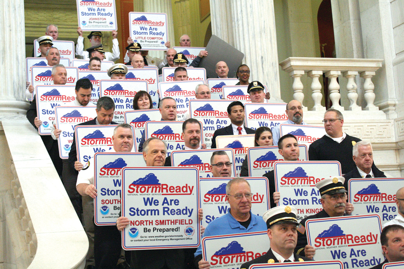 "DEPARTMENTS UNITE: Representatives from every city and town in Rhode Island, from Fire Chiefs to Town Managers, lined the State House stairs to be honored for being ""storm ready."" Cranston was represented by Chief William McKenna."