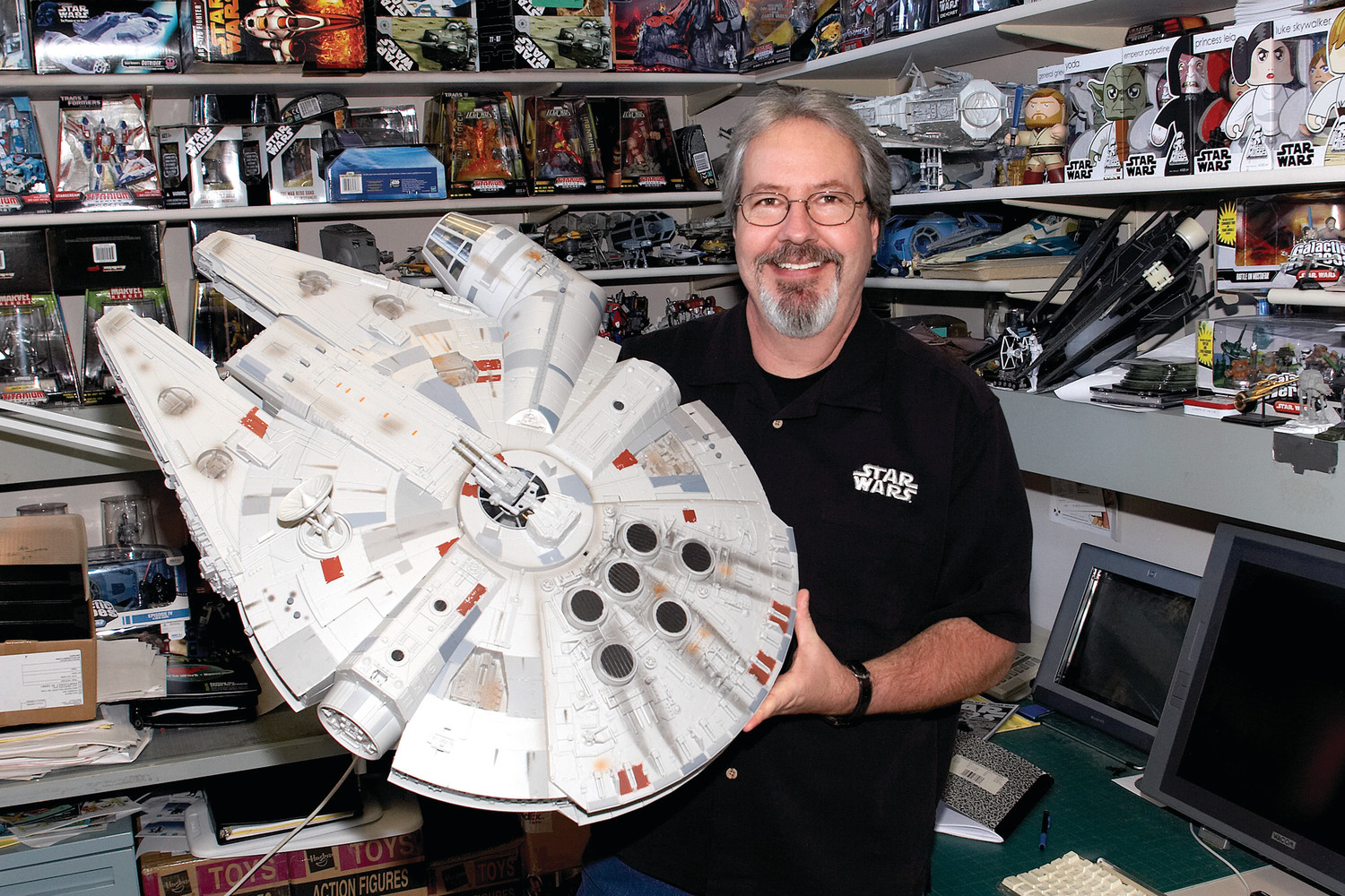 (2008) Boudreaux holds one of the Millennium Falcons that he designed in his office at Hasbro. New versions include updated paint schemes, enhanced mechanical play features, authentic light and sound effects, and even a pop-up Nerf launcher for The Force Awakens version.