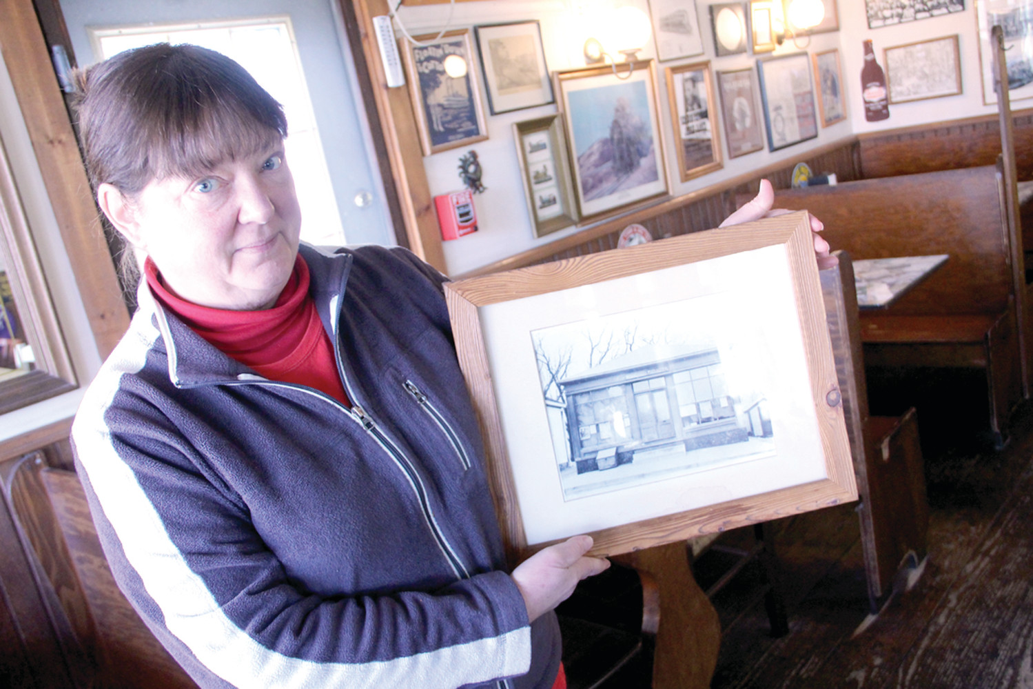 ONCE A POST OFFICE: Kathy Ruginski holds a photo of the Hillsgrove Post Office, now the Sandwich Junction. Kathy and her husband Craig bought the business from her parents in 1990. Ironically, Craig left the business to work for the post office in 2008.