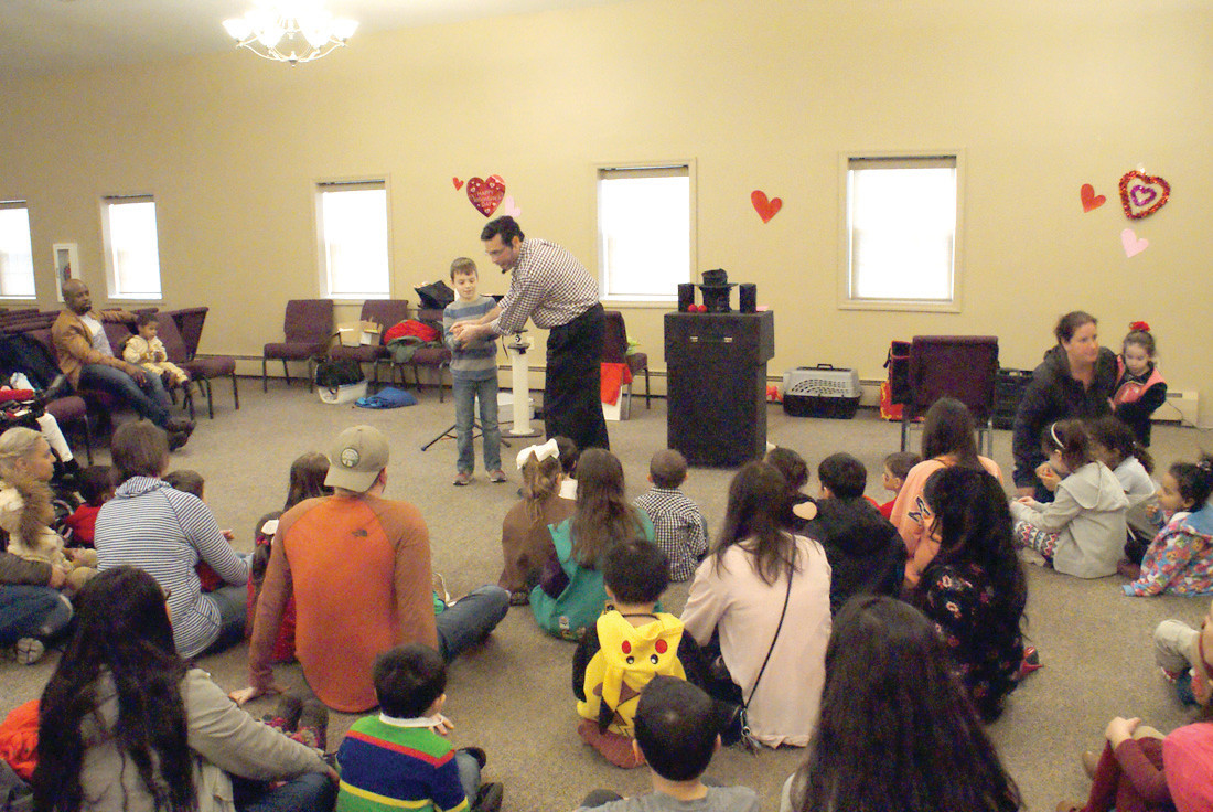 ENTERTAINMENT: Magician Steven Craig got assistance from audience member Nathan Tracey, age 7, during the 2nd Annual Magnolia Valentine's Day Family Celebration, hosted by Magnolia Pediatrics. Craig performed several magic tricks with Nathan's assistance.