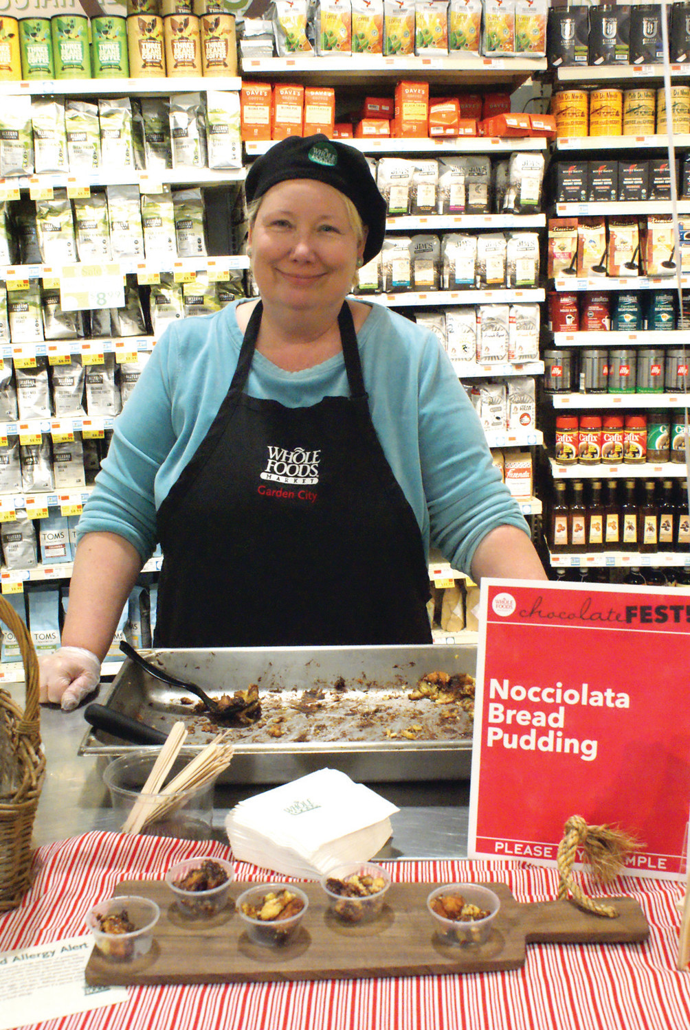 SERVICE WITH A SMILE: Whole Foods Cranstons Chocolate Fest Coordinator, Jennifer Goff, who is also a demo specialist for Whole Foods, serving free samples of store made chocolate hazelnut bread pudding.