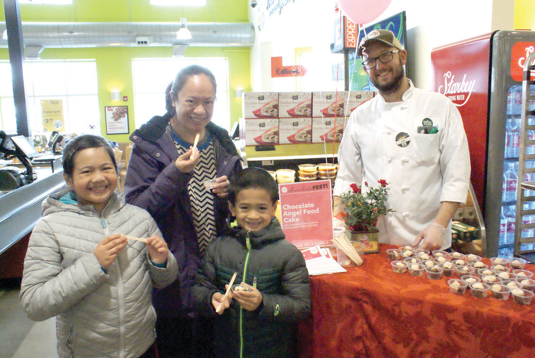 A LITTLE BIT OF HEAVEN: The Liwanag Family enjoyed their sampling of chocolate angel food cake which was angel food cake with a special chocolate sauce and chocolate whipped cream being served by Bakery Team Member at Whole Foods Cranston, Joel Henry. Pictured are Noranne and her children, Amanda, age 9 and Andrew, age 6.