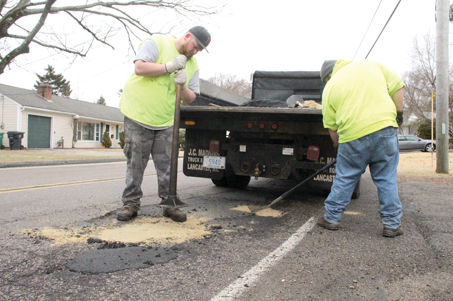 PATCH CREW: Swav Hermanowski and Chris St. Pierre fill potholes on Diamond Hill Road. Sand is used to cover the cold patch in an effort to reduce it from adhering to tires.