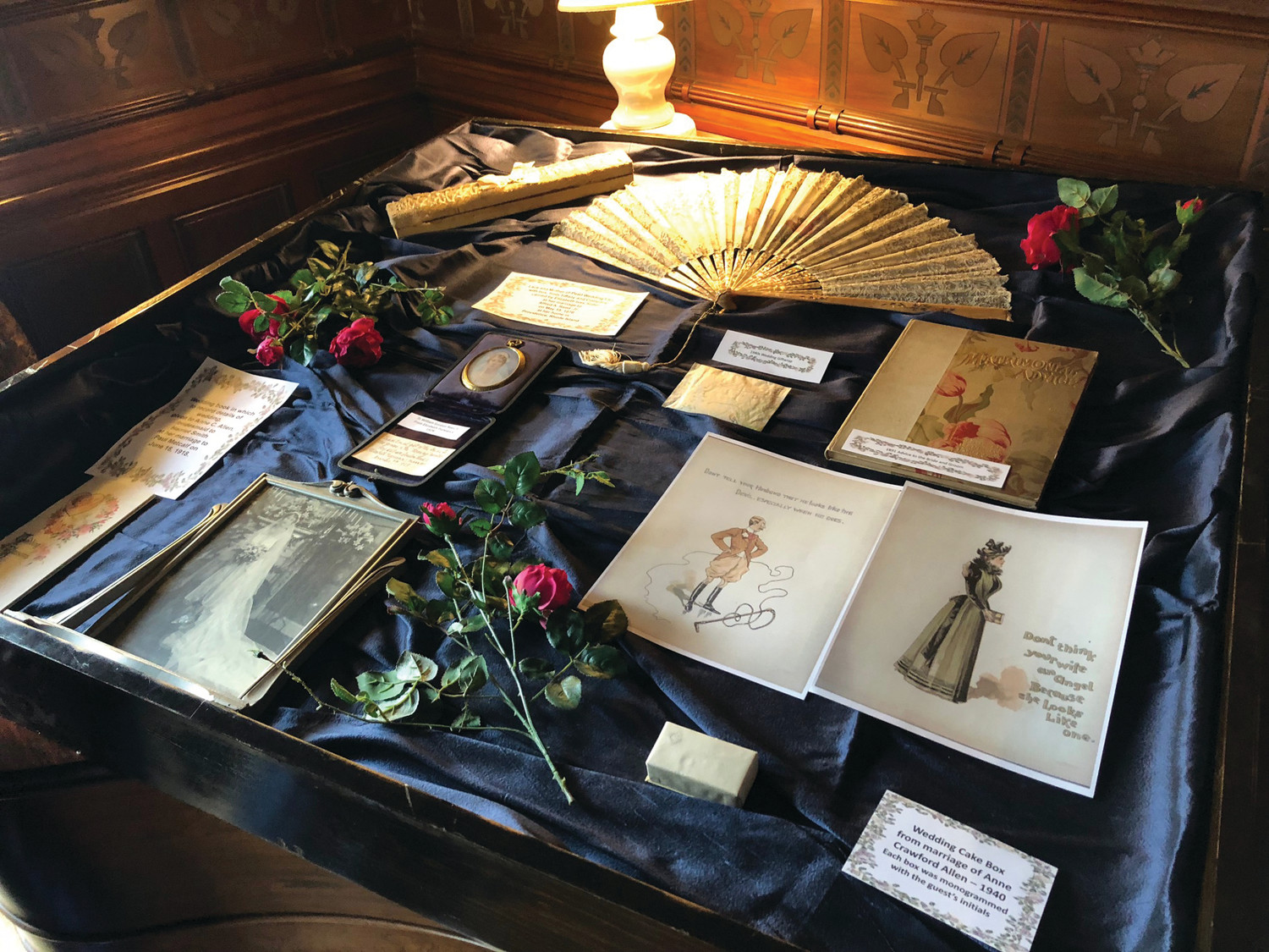 PARTY FAVORS: Included in this display is a Victorian-era fan and a monogrammed silver-ingrained party favor box, which Dietrich-Holst found still had a piece of fruit cake inside. She did not sample to see if the myth of its longevity held true.