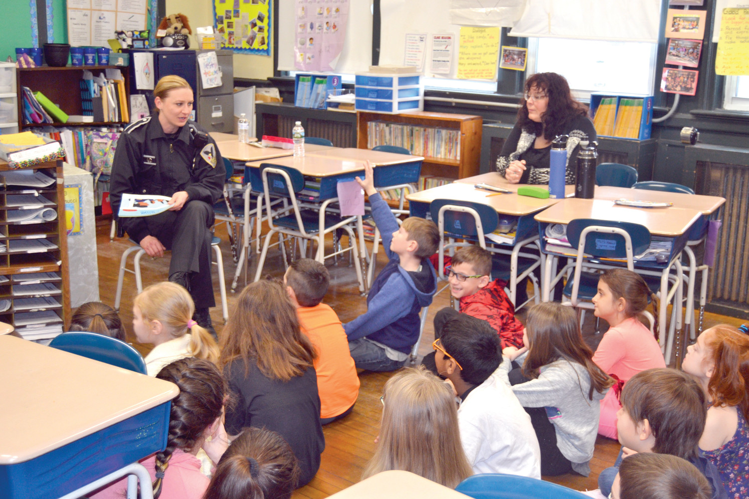 SAFETY FIRST: School Resource Officer Brooke Ardito (left), pictured here reading Keeping You Safe to students at Brown Avenue School, is one of two resource officers stationed at the high school and middle school. Ardito has the authority to respond to emergency situations at any of Johnston's schools.  (Sun Rise photo by Tim Forsberg)