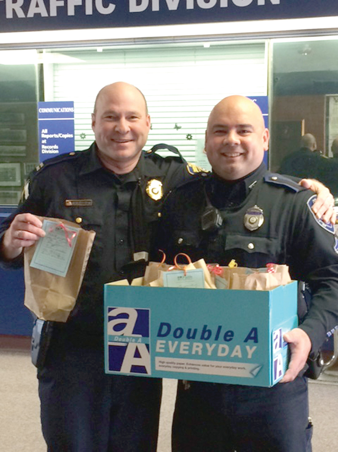 HAPPILY HUNGRY: Warwick Officers Joe Hopkins and Mark Jandreau happily except their personalized bags of cookies made from scratch by the parishioners at Faith Baptist Church.