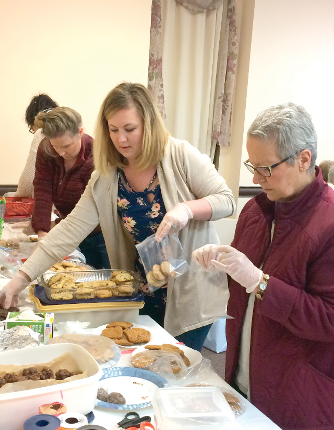 HARD AT WORK: Faith Baptist parishioners Renee Delfino, Connie Johnston, Mahria Pearson and Dolores Miller bag up the homemade cookies on Saturday.