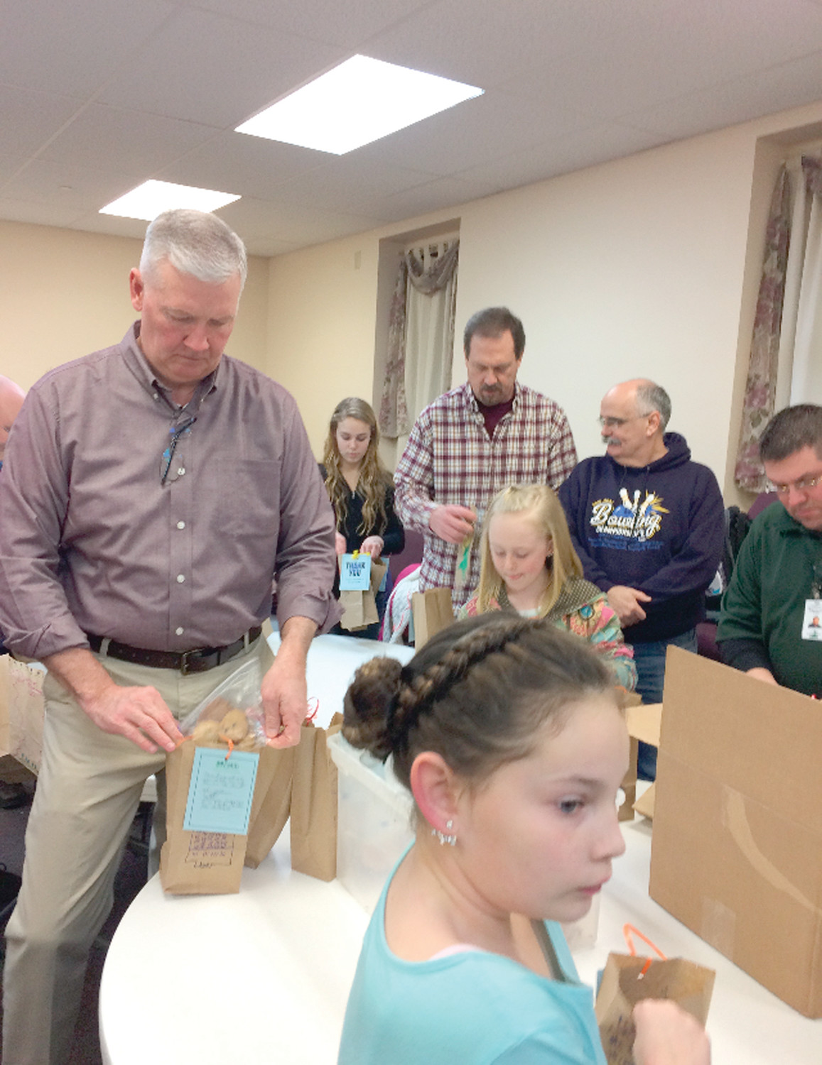 HELPING HIS OWN CAUSE: Police Captain Michael Higgins helps put the cookies into bags during the potluck dinner event at the church Saturday night, which would later be delivered to the police department on Tuesday afternoon.