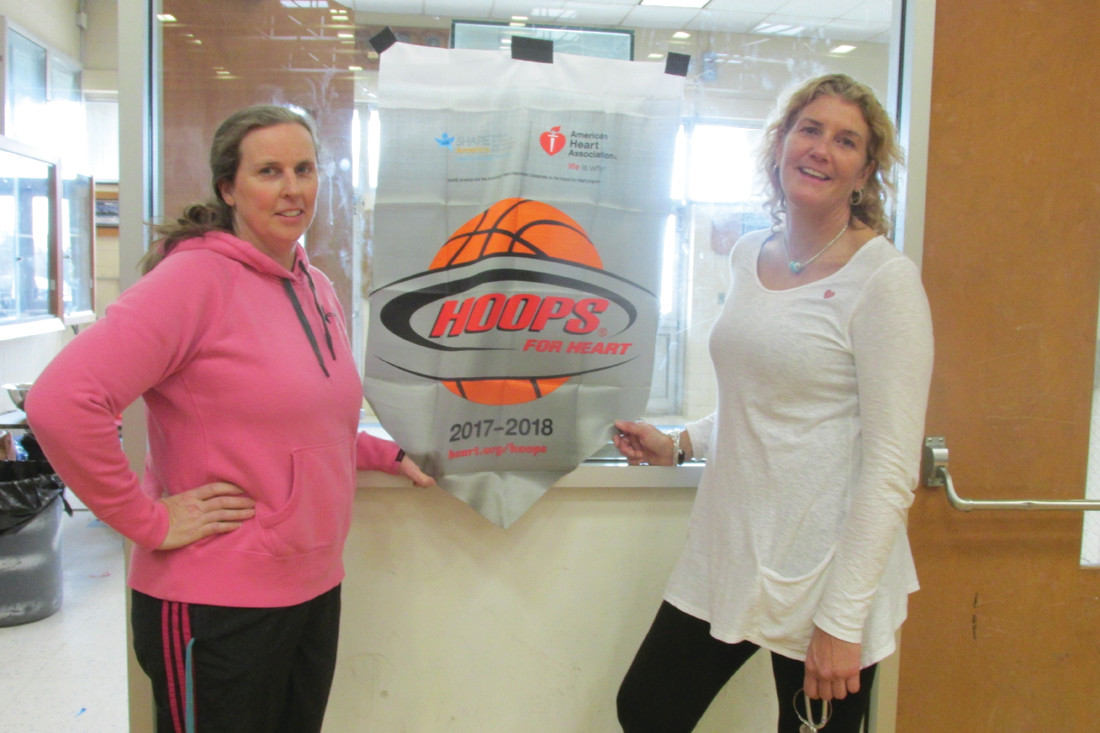 SUPER SUPPORT: Phys Ed teachers Peg Guilmette (left) and Ellen Quantmeyer stand beside a special promotion poster for the recent Hoops for Heart that they helped make an overwhelming success at Johnston High School.