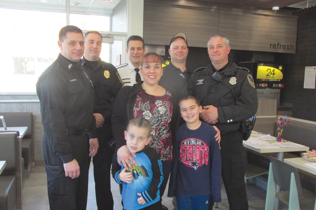 SUPPORT STAFF: Jennifer Liggett and her sons Nicholas and Christopher welcome Johnston Police officers Chuck Psilopoulos, Luca Lancellotti, Capt. Richard Norato, Bob Hay and David Slinko to Saturday's special promotion that included the fingerprinting of young children courtesy of the Crisafi family and JPD.