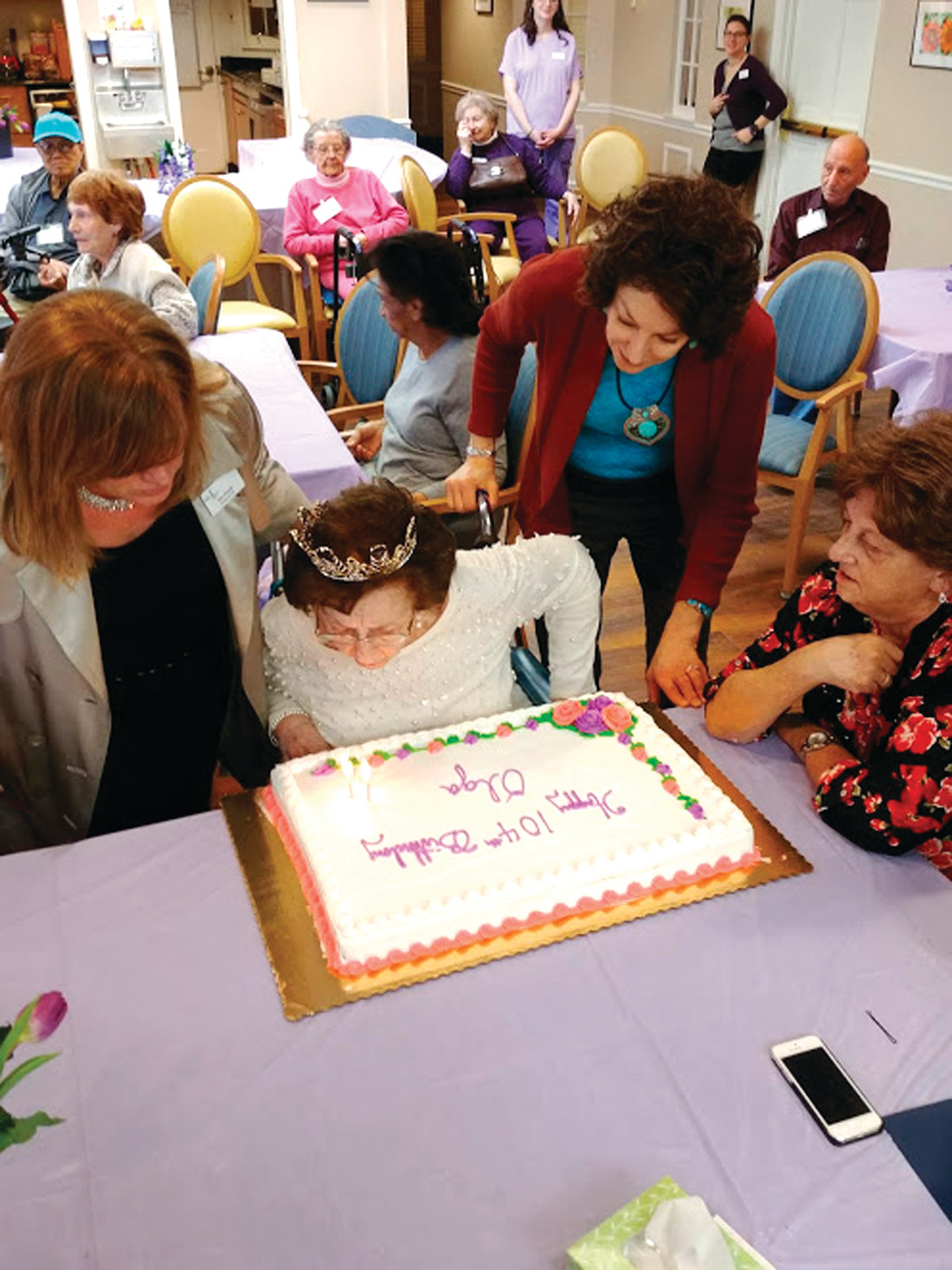 MAKING A WISH: Susi blows out the candles on her cake, which commemorated 104 years of living. She is assisted by her daughter, Anita, and Ellen Grizzetti, president and CEO of the Hope Alzheimer's Center in Cranston.