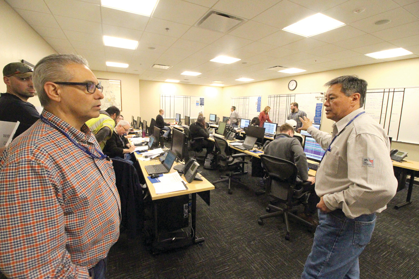 CENTER OF ACTIVITY: Nate Kocon (at right) directed those manning phones at the downed wire room of the National Grid storm center.