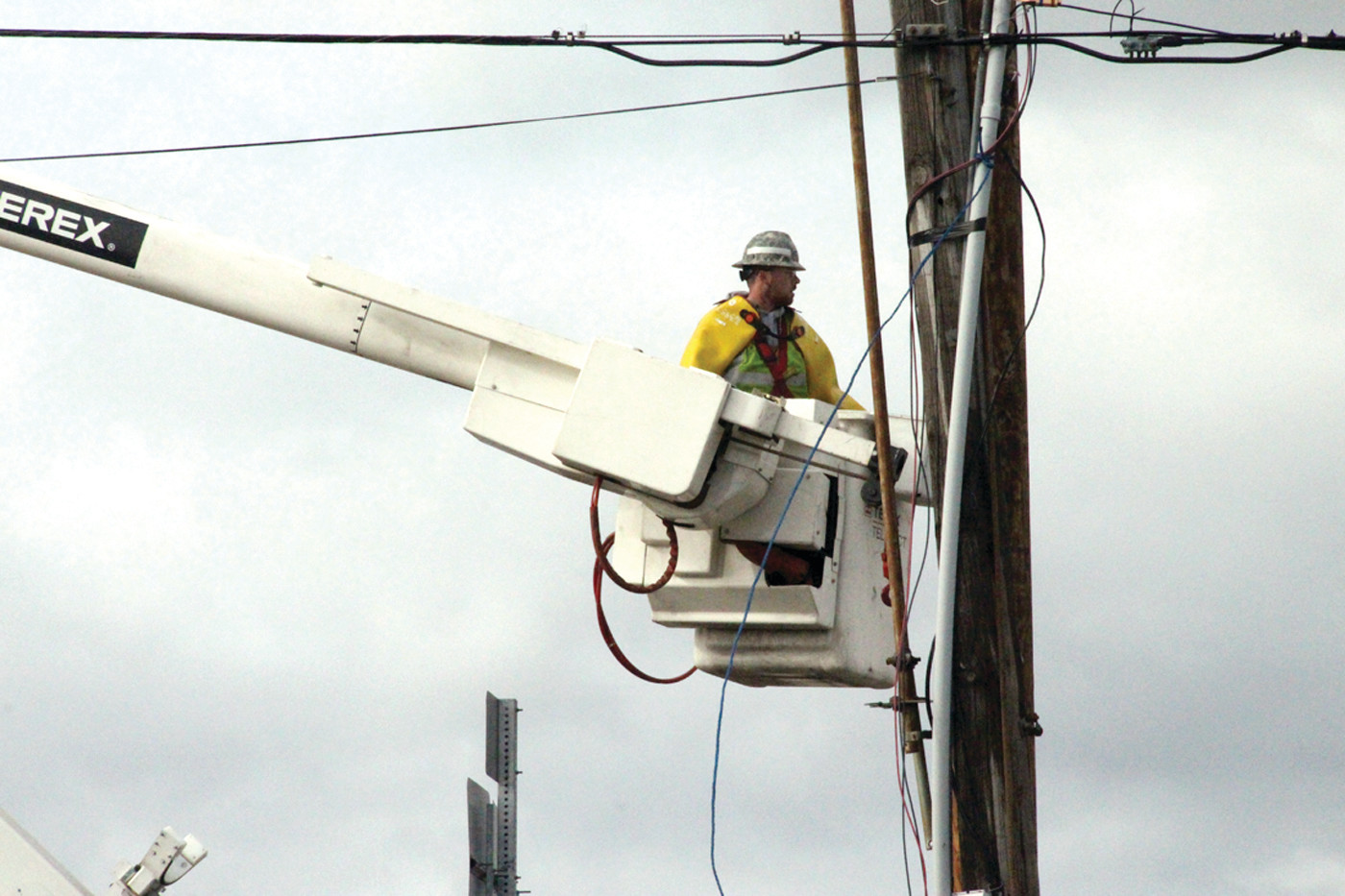 HIGH WIRE SHOW: National Grid lineman Bobby Kreamer works to secure a utility pole near the Cranston Police station.