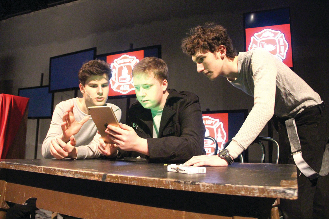 "THE ACTOR'S PROCESS: From left, Jack Ruschetta, playing ""fireman"" Black, Brendan Lawrence, playing Captain Beatty, and Jacob Boblitt, playing Holden, prepare for their roles together in a rehearsal Wednesday night for this weekend's production of Fahrenheit 451 at Hendricken."