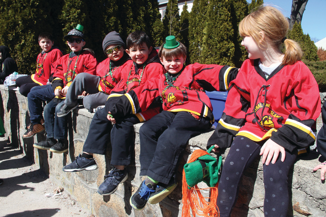 COOLING THEIR HEELS: The Rhode Island Central Knights Hockey find a convenient seat while waiting for the parade to start.