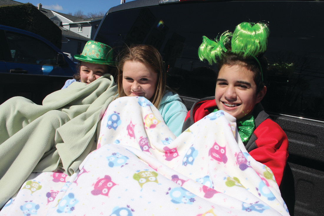 THEY DIDN'T NEED TO BUNDLE UP: Angie Santos, Riley Banes and Samie Rohar found a comfy spot to watch the parade from a truck bed with a blanket.