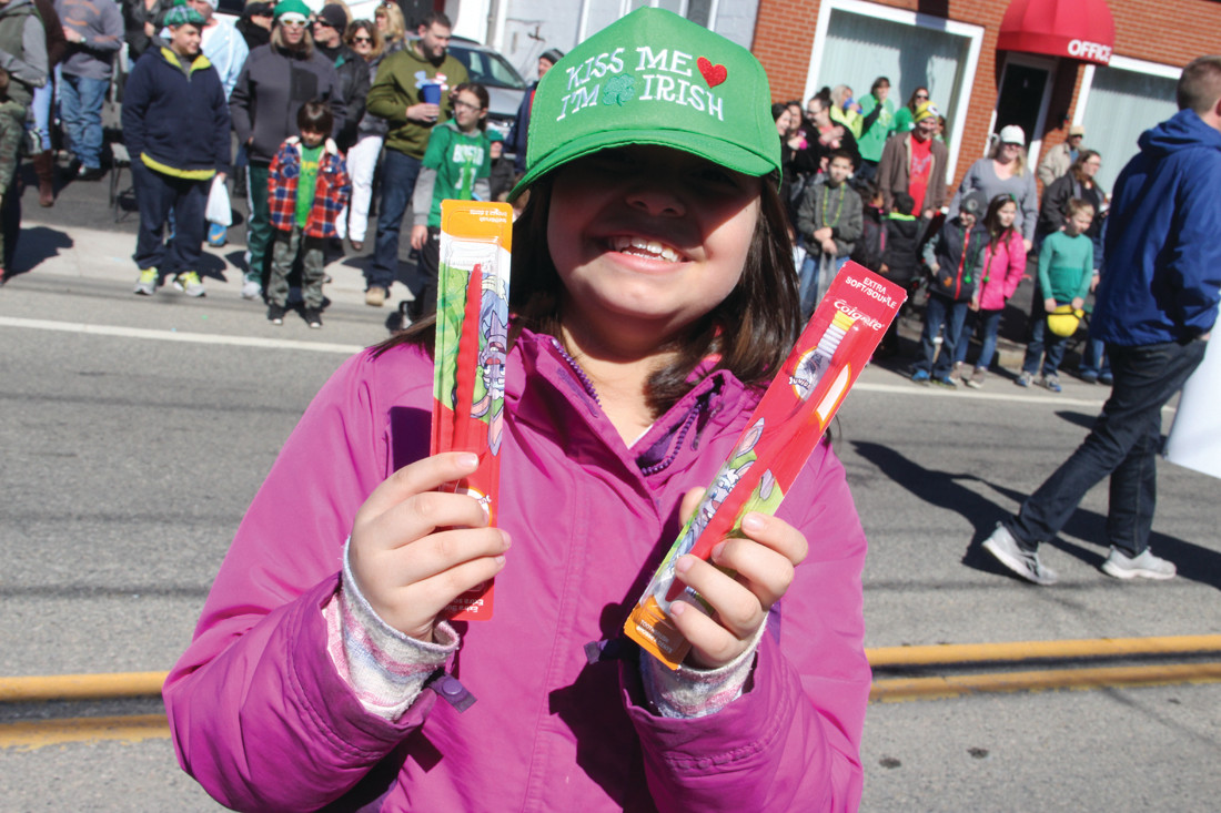 ANSWER TO CANDY: Addison Oreonez proudly hold up a couple of toothbrushes that were thrown to the crowd along with candy.