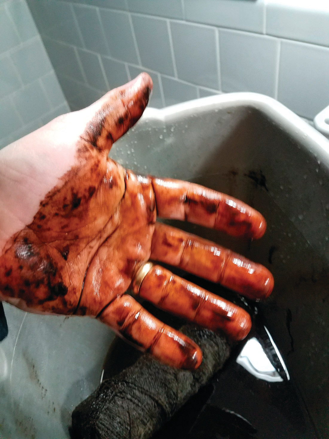 THAT'S NOT COFFEE: In a photo he provided, Michael Hackett of Cowesett shows the stains left on his hands following the removal of a home water filter. The cause is manganese, a naturally occurring mineral in area well water provided by the Kent County Water Authority.