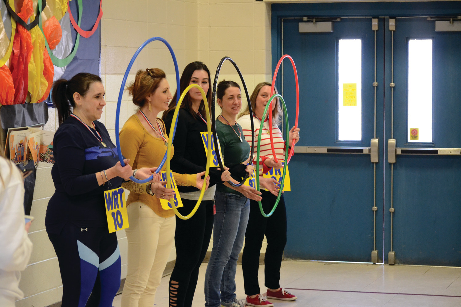 "RING LEADERS: Parent volunteers (from left) Kathy Mihalos, Jessica Weaver, Jessica Hemond, Andrea Merril and Christine Sturtevant held the ""Olympic Rings"" and helped put the whole show together."