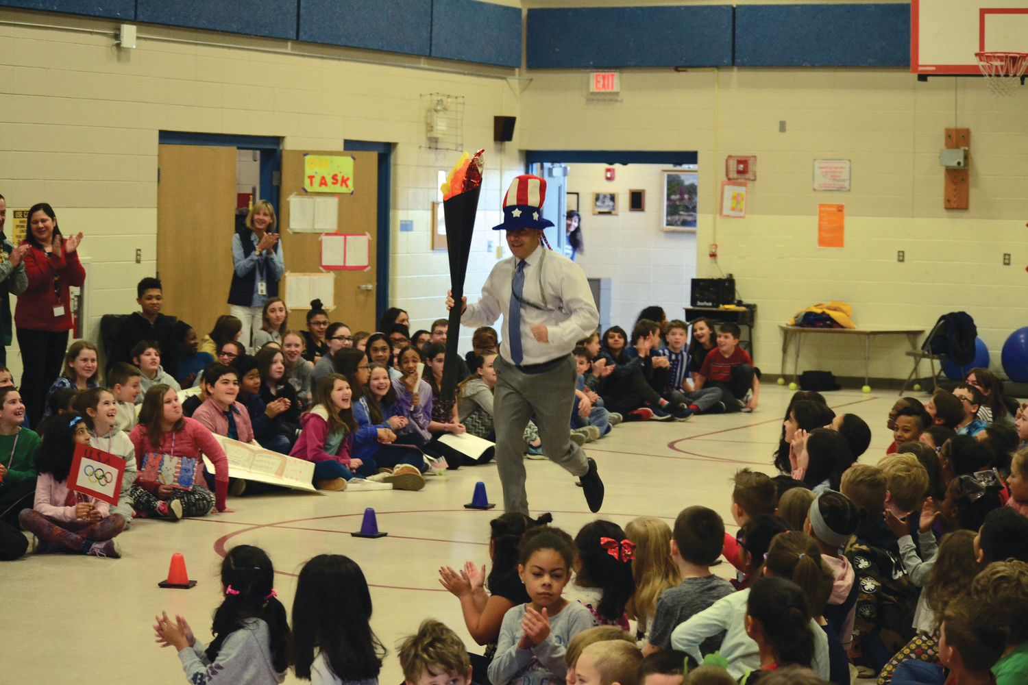 "A FIRE LITERATURE: Wyman Elementary principal Ron Celio carries the ""Olympic Torch"" during the opening ceremony of the school's annual Read-a-Thon on Monday morning, gathering loud cheers from the students, parents and faculty gathered."