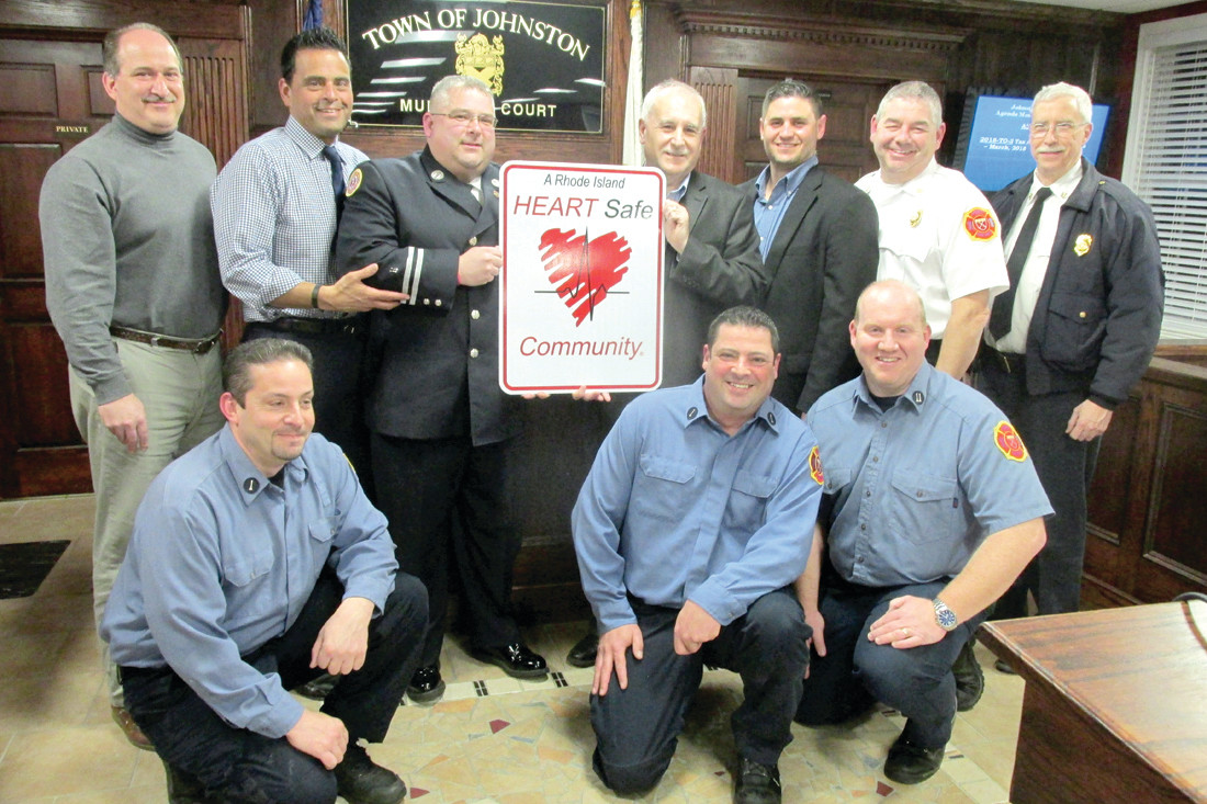 HISTORIC HAPPENING: Mayor Joseph Polisena holds the HEARTsafe sign with East Providence FD Captain John Potvin. They're joined by Councilman Robert Civetti and Robert Russo, Richard DelFino, David Iannuccilli and JFD Chief Peter Lamb. It front is John Jasparro, Jon Pistacchio and Keith Calci, officers of Local 1950 whose group has purchased many of the town's new AEDs. (Sun Rise photos by Pete Fontaine)