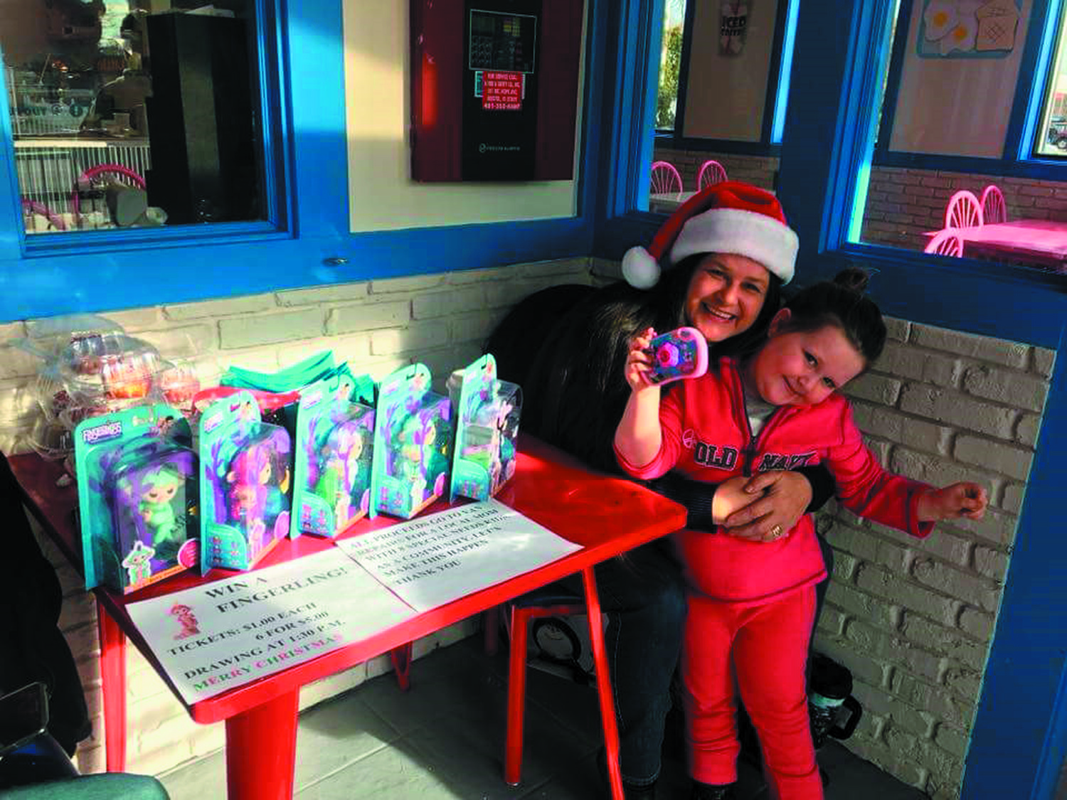 "FINGERLING FUNDRAISING: Marie Cavanaugh and Lila James, daughter of Jessica James, an administrator of the Positive Warwick Facebook page, raising money for ""Operation Fix the Van"" at 4corners Coffee in Warwick prior to Christmas."