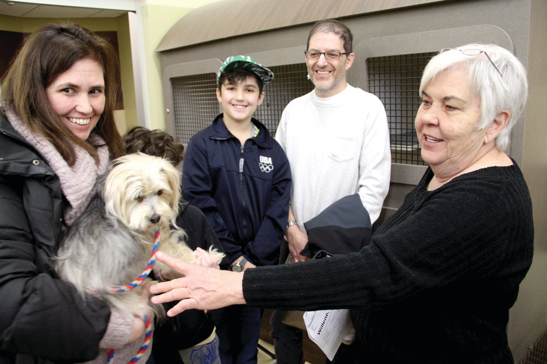 A NEW FAMILY: Willene Colvin (at right) talks with Ann Williams, brothers Owen and Nathaniel Schwartz and their father Dean Schwartz, who adopted one of the dogs Willene rescued in Georgia and delivered to Warwick Saturday.