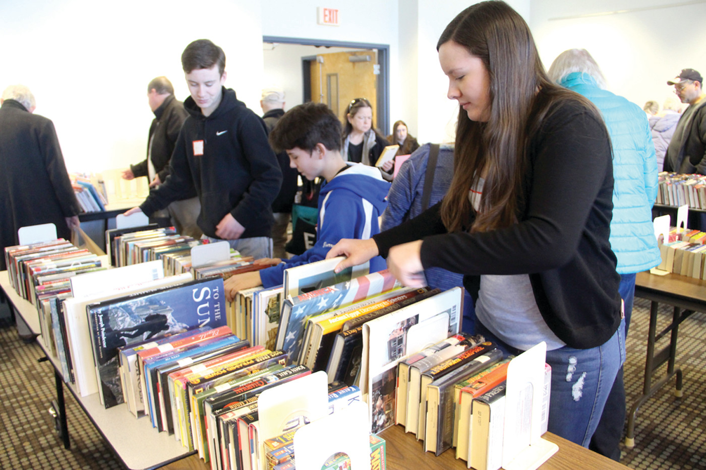 PUTTING IN THE HOURS: Veterans Junior High students Aaron Narcavage, Dylan Bourret and Maddy Narcavage straightened out table displays of hundreds of books, replenishing them as buyers made their selections to fulfill school service hour requirements.