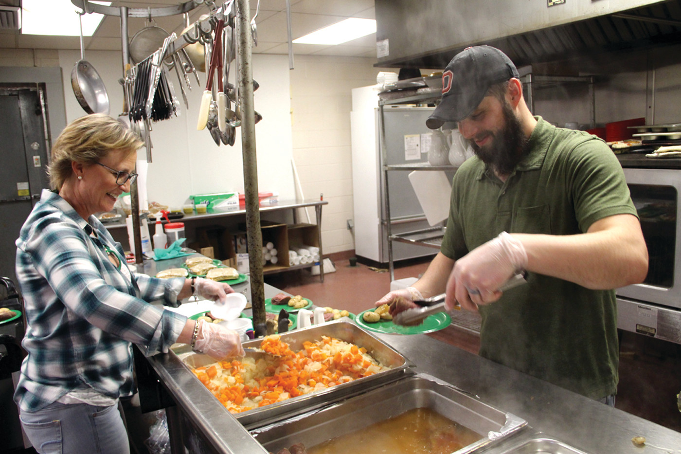 AN IRISH MEAL: Volunteer Rhonda McNamara and chef Kevin Boyes plate the corned beef lunches served at the Pilgrim Senior Center Friday.