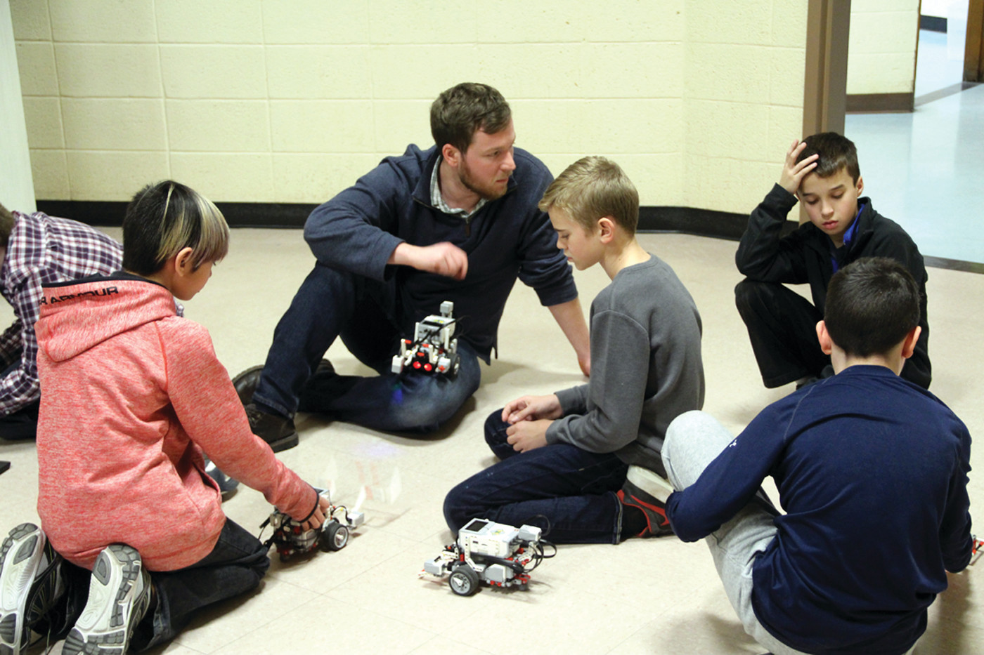 IN THE THICK OF IT: Toll Gate teacher Adam Ricci was on the floor with Scott School students and their robots. Ricci said the kids take quickly to building robots and he sees the after school activity as a good feeder to STEM (science, technology, engineering and math) curricula at the middle and high school levels.
