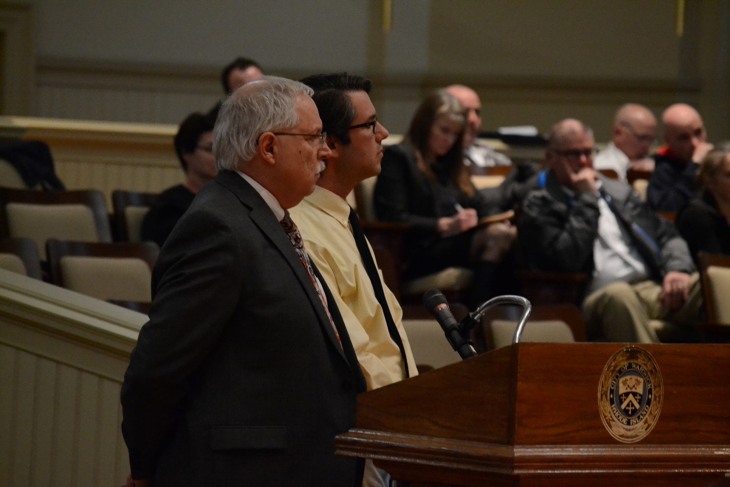 FIRM STANCE: Anthony Ferrucci, school finance director (left), and Doug Alexander, school technology director, listen to inquiries from Councilman Howe on Monday night in the council chambers.
