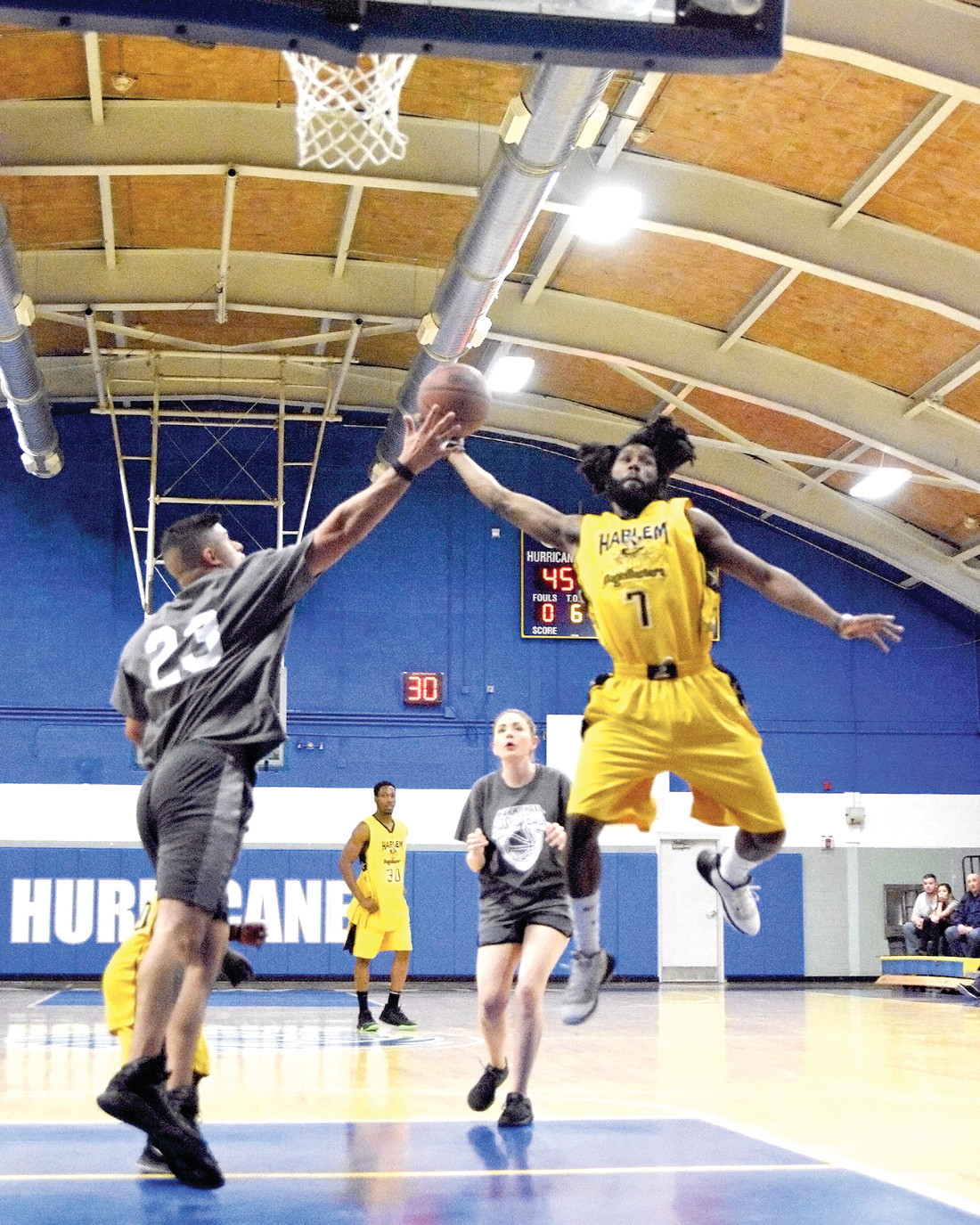 BLAST OFF: Kaseem Williams (number 7) goes up tall for a bucket against a defending Ali Jafaar of the Warwick Police Athletic League (number 23).