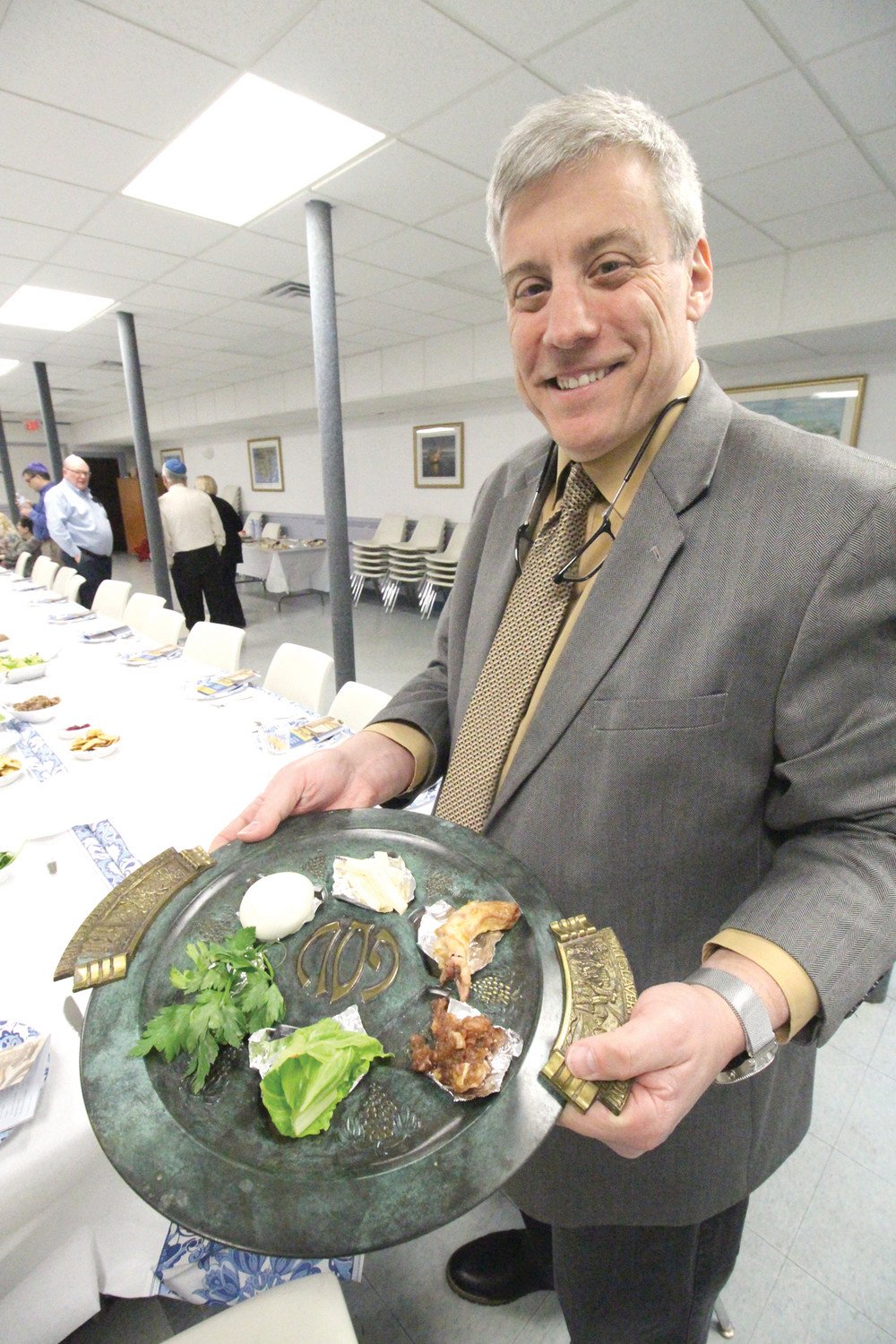 THE SEDER PLATE: Michael Frank, president of the Jewish Congregation Or Chadash, holds the Seder plate that includes a hard-boiled egg, roasted shankbone, bitter herbs, charoses or mixture of finely chopped apples, nut and cinnamon, chazeres or romaine lettuce and karpas or parsley or celery. Each of the foods has symbolic meaning with the egg representing spring and a new beginning.