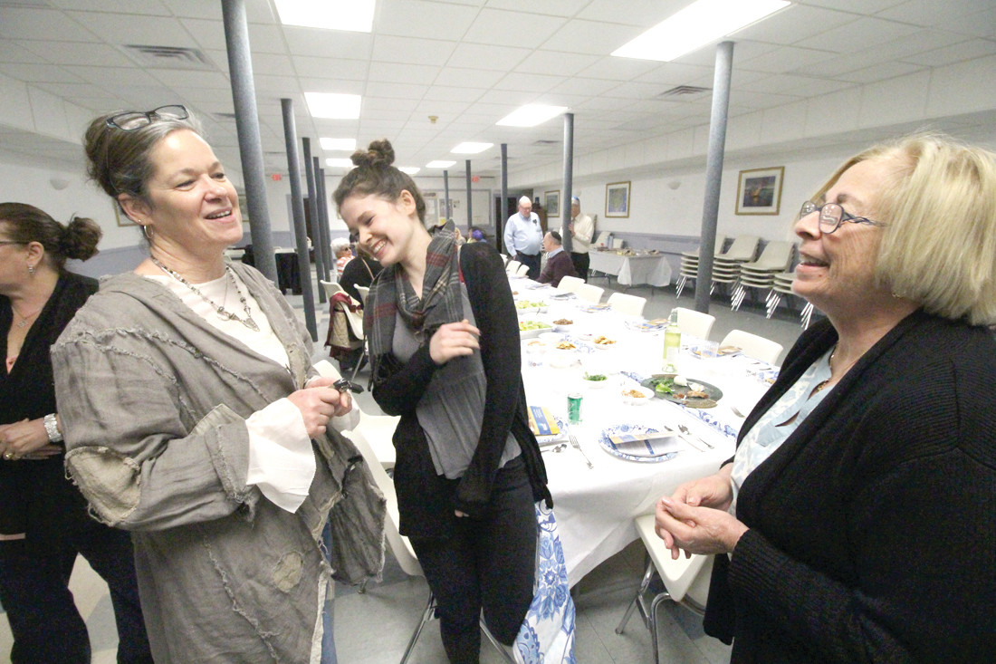 ALL ARE WELCOME: Judith Bessof, at right, shares a moment with the Rev. Johanna Marcure, pastor of Trinity Episcopal Church in Scituate and her daughter Leah Tabor at the Sedar at Trinity Church in Pawtuxet.